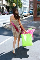 Back view of young brunette woman in a summer dress crossing a street carrying shopping bags