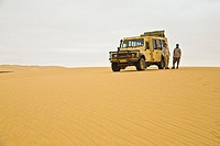 A landrover and two people in the desert of the Skeleton Coast Park, Namibia, Africa