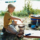 Boy cooking outside during picnic