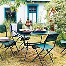 Plates with fruits and vegetables on garden table