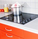 Metal pot on electric glass cooker in domestic kitchen