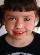Portrait of girl with face stained with dough