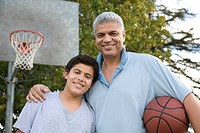Hispanic father and son with basketball