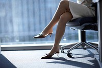 Businesswoman sitting on chair, low section