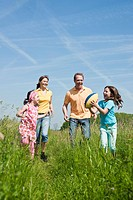 Family throwing football on a meadow