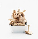 A white bowl with mushrooms against white background.