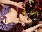 High fashion photo of a beautiful woman lying on a festive table and eating grapes