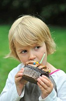 Little girl eating chocolate cupcake