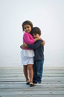 Young brother and sister hugging