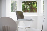 Laptop on modern, white dining room table