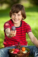 Germany, Boy 10_11 Years smiling with easter egg basket, portrait
