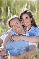 Germany, Bavaria, Man and woman embracing in meadow, smiling, portrait