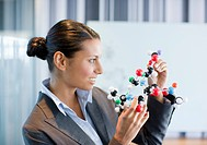 Businesswoman looking at molecule model