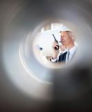Businessman in hard_hat talking on walkie_talkie outdoors