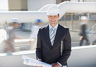 Businessman in hard_hat holding blueprints outdoors