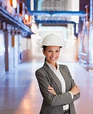 Businesswoman in hard_hat standing in factory