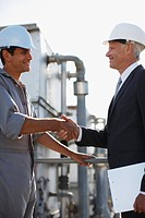 Businessman in hard_hat shaking hands with worker outdoors