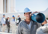 Worker in hard_hat carrying large pipe outdoors