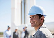 Worker in hard_hat standing outdoors