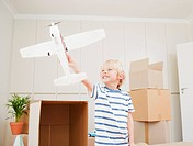 Boy playing with model airplane in new house