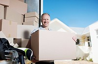Smiling man carrying box from moving van (thumbnail)