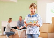Girl holding fish bowl in her new house