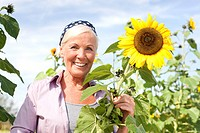 Germany, Saxony, Senior woman with sunflower, smiling