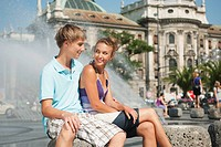 Germany, Munich, Karlsplatz, Young man and woman sitting at fountain