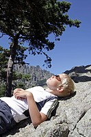 Young boy lying in sun in the Corsican mountains