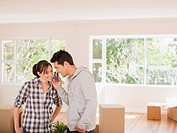 Couple talking on cell phone in new house