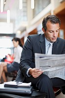 Businessman reading newspaper in hotel lobby