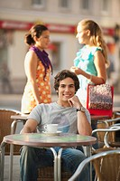 Germany, Munich, Young man at cafe smiling with friends in background