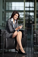 Germany, Bavaria, Business woman with mobile, smiling