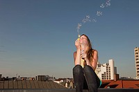 Germany, Bavaria, Munich, Young woman blowing bubbles