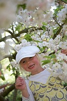 Girl standing by blossom tree