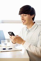 Man using smart phone in home office.