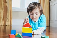 Young boy building a house with colourful blocks.