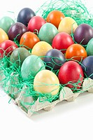 Variety of easter eggs in egg carton on white background