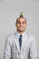 Businessman smiling with a sapling over his head
