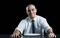 Businessman sitting at a dining table and smiling