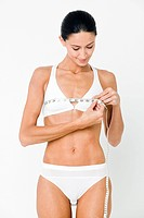 Young woman measuring breasts with tape measure