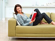 Mature woman sitting on sofa reading book