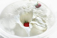 Strawberries dropping into milk, close up