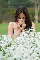Close_up of a woman sneezing near flowers
