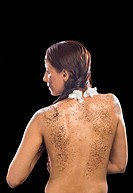 Rear view of a woman with tea leaves on her body