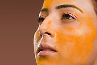 Close_up of a woman with turmeric on her face