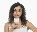 Woman holding a glass of milk and licking lips