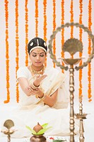 Bride praying in traditional South Indian dress