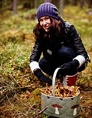 Sweden, Halsingland, portrait of woman picking mushrooms in forest