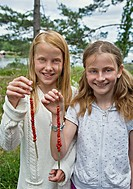 Sweden, two girls 10_11, 12_13 holding grass strew with wild raspberries and looking at camera